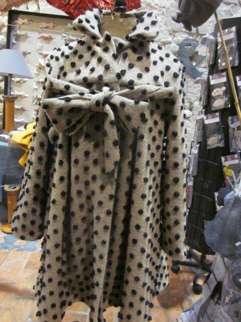 Un manteau AGLAE en lainage maille beige à pois noirs fermé par un noeud...