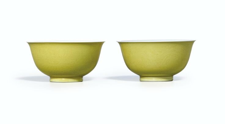 A pair of incised yellow-glazed 'dragon and phoenix' bowls, Marks and period of Yongzheng