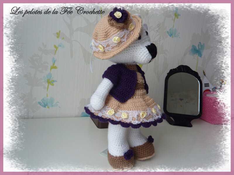 Elle est habillée d'une jolie robe à bretelles et d'un gilet violet.