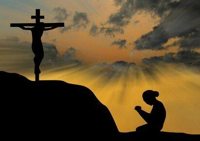 femme à genoux devant la croix