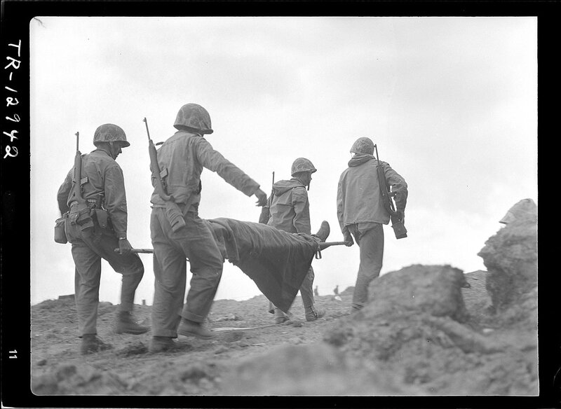 1280px-Transportation_of_wounded_on_Iwo_Jima__A_wounded_Marine_being_evacuated_from_front_lines_for_medical_treatment__-_NARA_-_520734