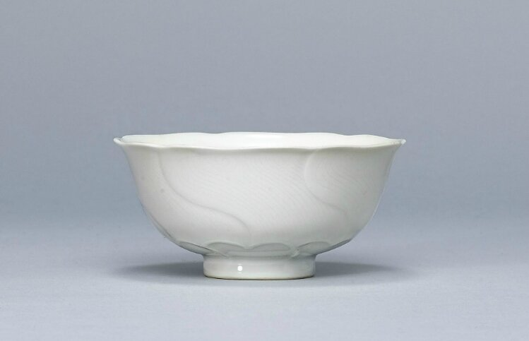 A white-glazed flower-form cup, Yongzheng six-character mark in underglaze blue within a double circle and of the period