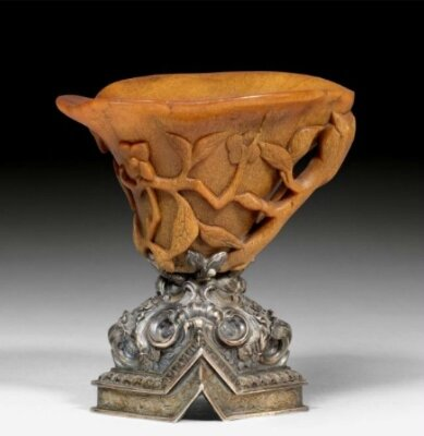 A carved rhinoceros horn libation cup with silver foot