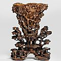 A fine light amber rhinoceros horn libation cup with four immortals and prunus, bamboo and pine with magnolia and rocks, 17th century